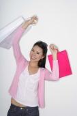 woman holding up shopping bags - Yukmin