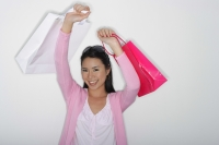 woman holding up shopping bags - Yukmin