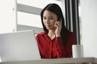 woman working at laptop, talking on phone - Yukmin