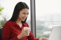 woman with coffee at laptop - Yukmin