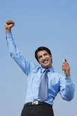smiling business man with fist in air, phone in hand - Alex Mares-Manton