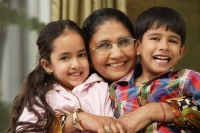 grandmother hugs grandkids, all smile at camera - Alex Mares-Manton
