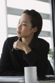 woman at desk, pen to chin - Yukmin