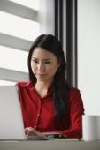 woman looking down at computer screen - Yukmin