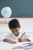 boy at desk with colored pencils - Alex Mares-Manton