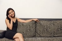woman sitting on couch talking on phone - Alex Mares-Manton