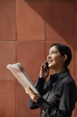 woman talking on phone, holding newspaper - Alex Mares-Manton