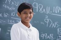 boy in front of chalkboard smiling - Alex Mares-Manton