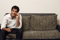 man sitting on couch talking on phone - Alex Mares-Manton