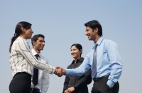 four business colleagues, two shaking hands - Alex Mares-Manton