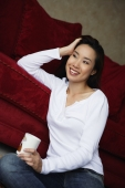 woman sitting on floor holding coffee cup - Yukmin