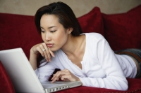 woman working on laptop on couch - Yukmin