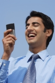 businessman reading message, laughing - Alex Mares-Manton