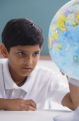 boy looks at globe, one hand on globe - Alex Mares-Manton