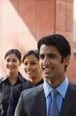 one businessman in foreground, two businesswomen in background, all smiling (vertical) - Alex Mares-Manton
