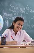teacher at desk, smiling at camera (vertical) - Alex Mares-Manton