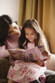 mother and daughter look at story book - Alex Mares-Manton