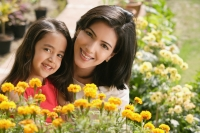 mother and daughter with flowers, smiling at camera - Alex Mares-Manton