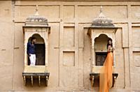 man and woman on balconies, woman in sari - Alex Mares-Manton