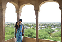 young couple leaning against pillar on terrace balcony - Alex Mares-Manton