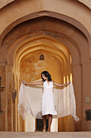 woman walking with shawl in arched hallway - Vivek Sharma
