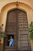 young woman standing at a huge wooden doorway - Alex Mares-Manton