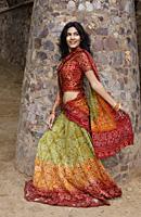young woman in sari walking, stone pillar - Alex Mares-Manton