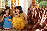 two young women chatting, wearing saris - Alex Mares-Manton