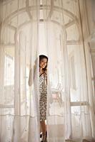woman peaking through curtains - Vivek Sharma