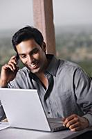 man on phone, working at laptop computer - Vivek Sharma