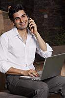 man on phone, working on laptop computer - Vivek Sharma