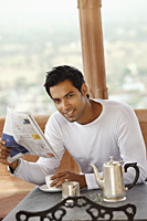 man reading morning newspaper, having hot drink - Vivek Sharma
