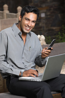 man with phone and laptop computer - Vivek Sharma