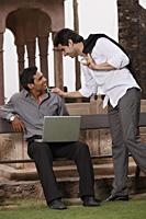 men talking outside, one working at laptop computer - Vivek Sharma