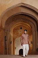 man walking up arched hallway - Vivek Sharma