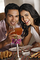 couple at restaurant, raising for a toast - Vivek Sharma