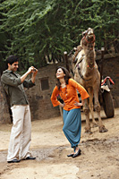 man taking photo of woman in front of camel - Vivek Sharma
