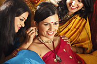 three women in saris, one placing jewelry on another - Vivek Sharma