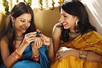 two women in saris, holding jeweled box - Vivek Sharma