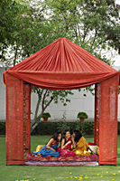 three young women in saris, chatting in tent - Alex Mares-Manton