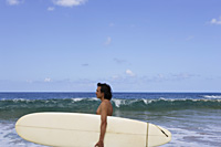 man looking out to sea, holding surf board - Yukmin