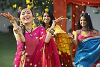 three women in saris, throwing petals - Vivek Sharma
