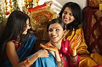 three women in saris, one showing her henna hands - Vivek Sharma