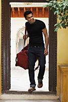 man coming through doorway with duffel bag - Vivek Sharma