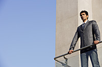 businessman standing at balcony - Alex Mares-Manton