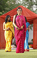 three women in saris in front of red tent - Vivek Sharma