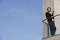 businesswoman with mobile phone, on balcony - Alex Mares-Manton