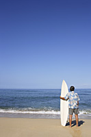 mature male surfer looking at sea - Yukmin