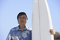 mature man standing next to surf board - Yukmin