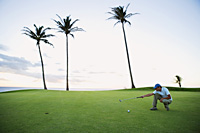 man squatting on golf course, judging angle - Yukmin